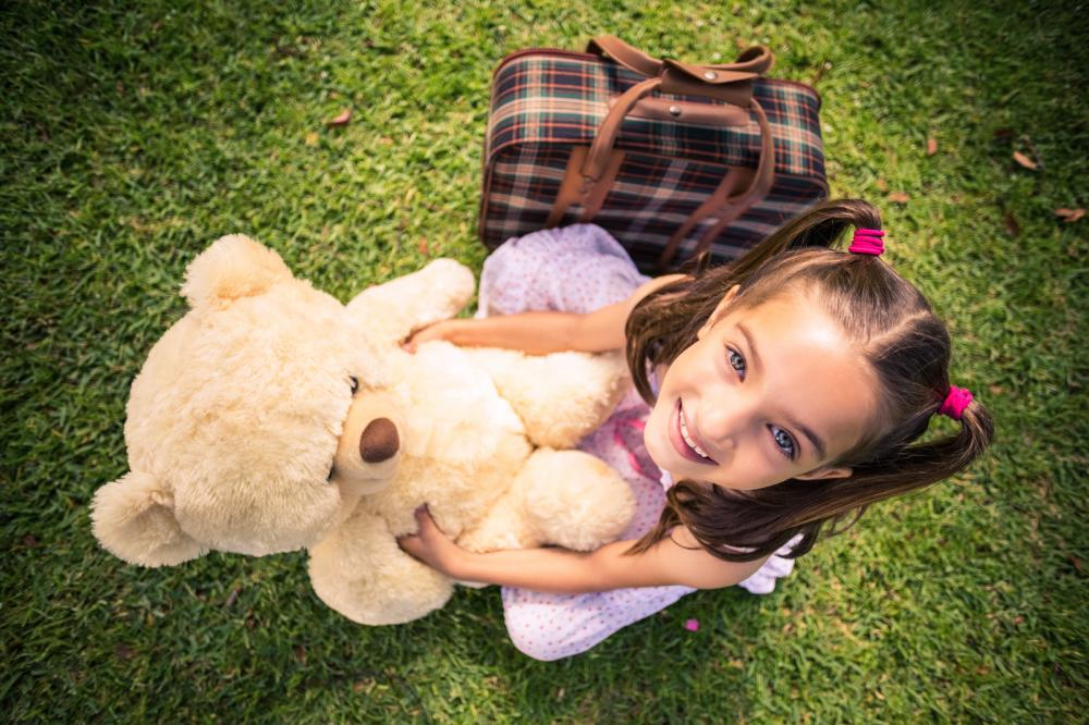 young-girl-sitting-with-a-teddy-bear-and-suitcase[1]